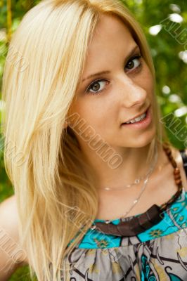 Portrait of a happy young woman posing in a park - Outdoor