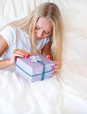 Bedroom surprise present - young happy woman in bedroom