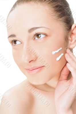 Portrait of a beautiful young woman applying cream to her face.