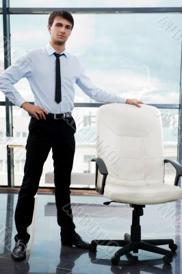 Portrait of confident businessman at his office standing near em