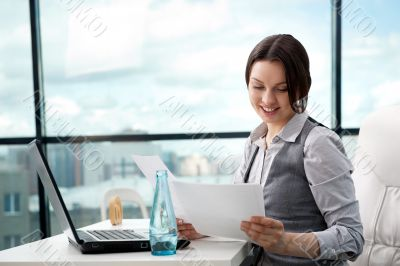 Beautiful business woman looking at papers she holding in her ar