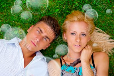 A portrait of a sweet couple in love with soap bubbles around. P