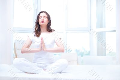 Young woman meditating with closed eyes in bright bedroom sittin