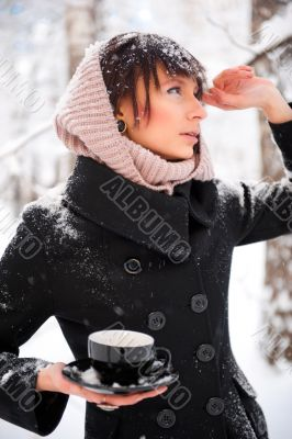 Portrait of young beautiful woman standing alone in winter park