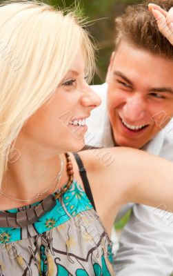 Romantic young couple sitting together in forest and smiling