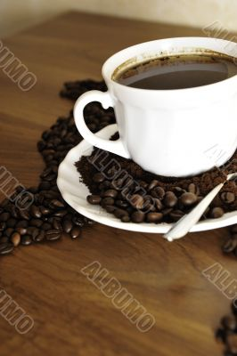 Dramatic photo of world map made of coffee beans. White cup with