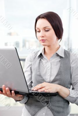 Beautiful business woman concentrating while working on computer