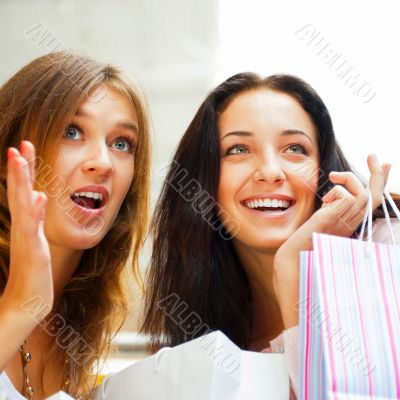 Two excited shopping woman together inside shopping mall. Horizo