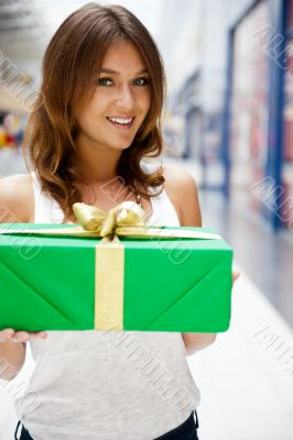 Portrait of young excited pretty woman standing inside shopping