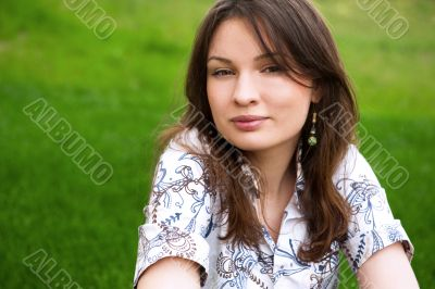 Closeup portrait of pretty young woman resting on grass and smil