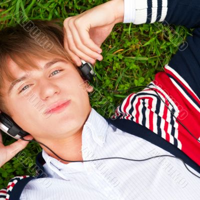 Student outside laying on grass and listening music school. Phot