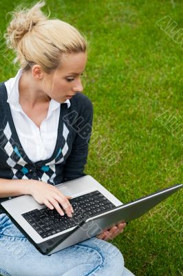Young woman with laptop sitting on green grass and looking to th
