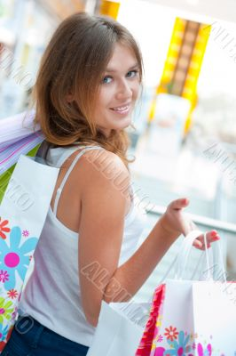 Happy shopping woman at the mall preparing gifts for her friends