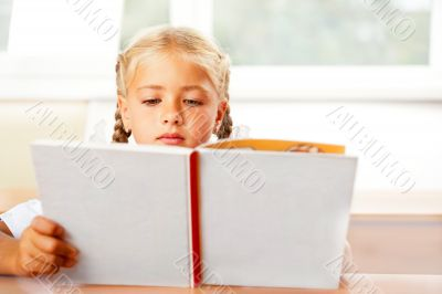 Image of smart child reading interesting book in classroom. Hori