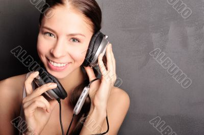 Club style woman with headphones listening to music looking at c