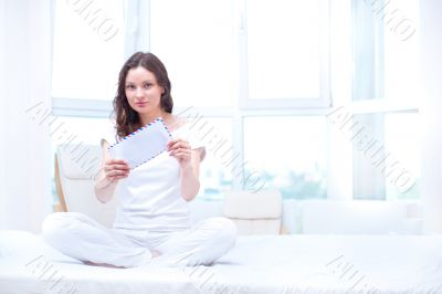 American or european young pretty woman sitting on bed in bright