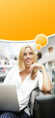 Portrait of happy blond woman using laptop at shopping mall cafe