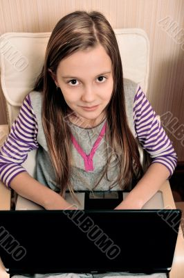 Young girl doing she`s work on laptop sitting on armchair