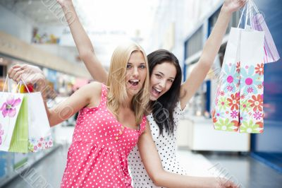 Closeup of two attractive happy girls out shopping