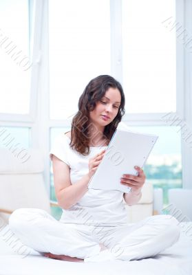 Young woman with a notebook studying at home