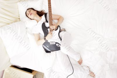 Teen girl holding a guitar like a rock star and enjoying playing