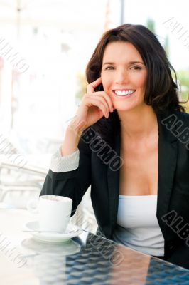 Closeup portrait of cute young business woman smiling while drin