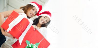 Young happy girls in Christmas hats.Standing together indoors an