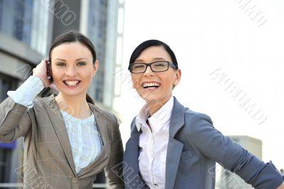 Portrait of two businesswomen outside.