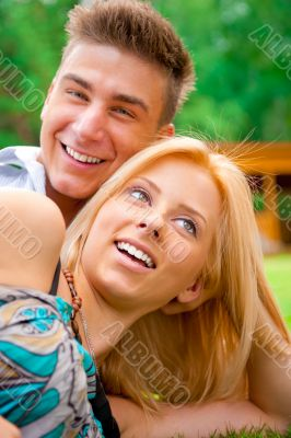 Portrait of beautiful young couple sitting on ground in park rel