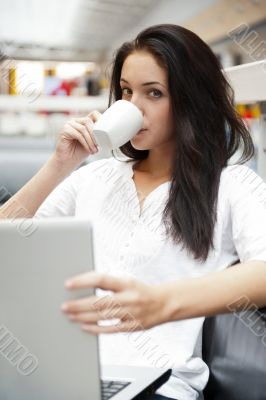 Portrait of a beautiful young woman working on laptop and drinki