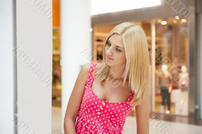 Beautiful shopping woman standing near informational stand insid
