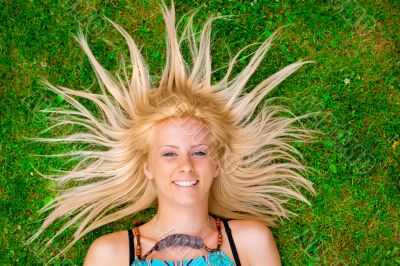 Young woman laying on green grass with hair like a sun around he