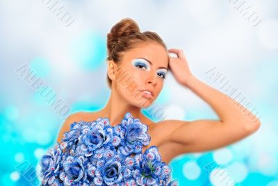 Gorgeous woman with blue flower dress over blurred shiny backgro