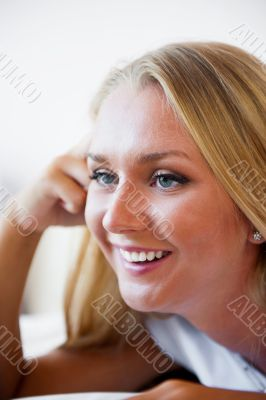 Portrait of beautiful smiling woman on bed at bedroom watching t