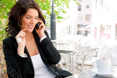 Portrait of young business woman sitting relaxed at outdoor cafe