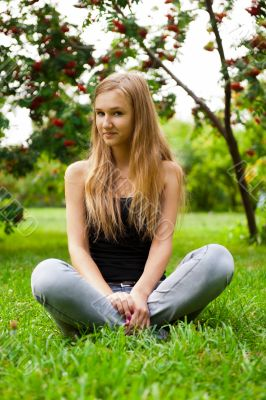 Beautiful female student outdoors sitting on grass at campus par