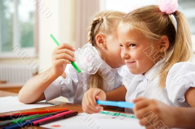 Two little girls gossip in classroom