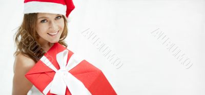 Young happy girl in Christmas hat. Standing indoors and holding