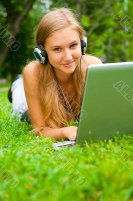 A smiling young girl with laptop outdoors listening music by hea