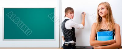 Two students - girl and boy making presentation at classroom