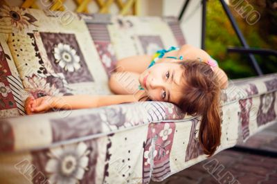 Artistic lifestyle photo of little girl leaning on swing sofa ou