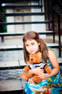Artistic lifestyle photo of cute little girl outdoor sitting at