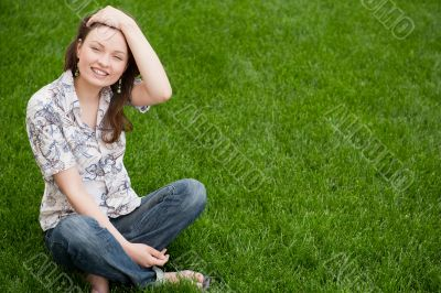 Full length of pretty young woman resting on grass and smiling