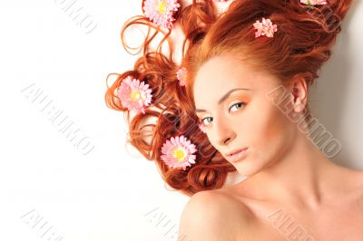 Beautiful woman with flowers in her red hair she is lying relaxe