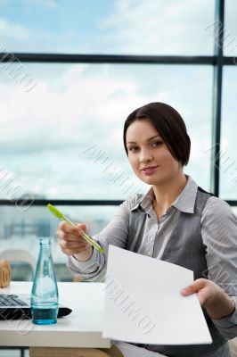 Portrait of a happy young agent giving pen and blank agreement t