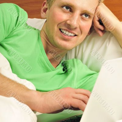 Attractive man relaxing in bed. White silk linen. Working by is