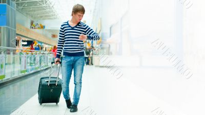 Portrait of a successful young man walking with travel bag at mo