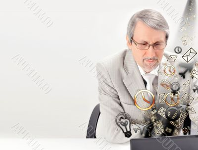 Closeup of a mature smiling business man sitting at his office a