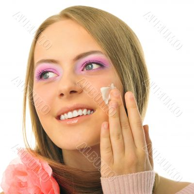 Beautiful woman applying moisturizer cosmetic cream on face - on