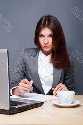 A pretty concentrated woman working with her laptop and papers.